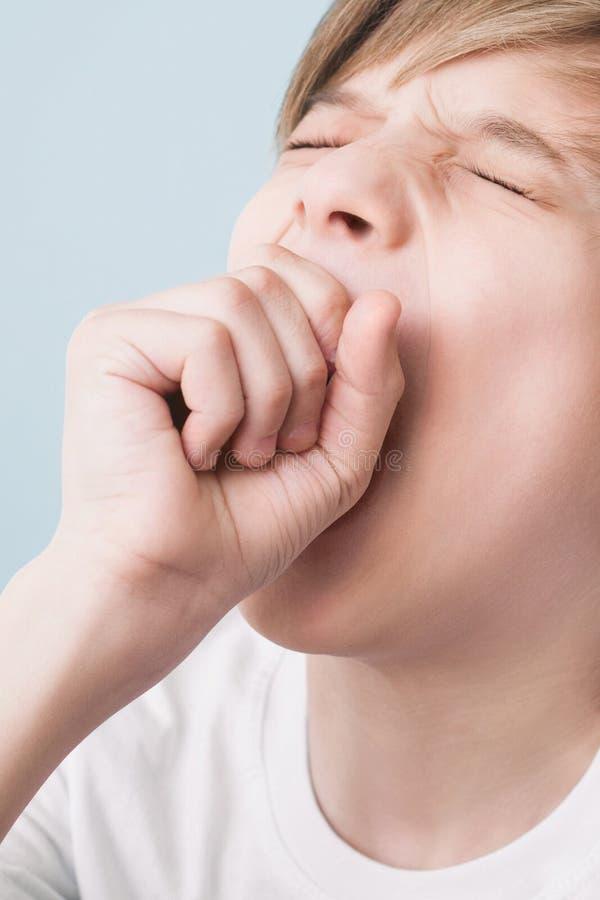 Il ragazzo sbadiglia largamente con i suoi occhi chiusi, coprendo la sua bocca di suo pugno fotografia stock libera da diritti