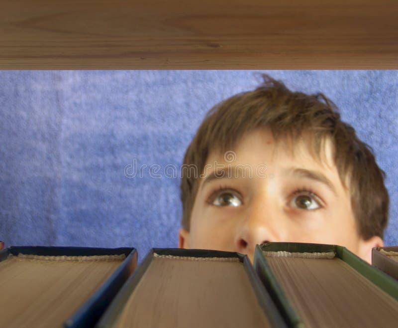 Il ragazzo sceglie un libro fotografie stock libere da diritti