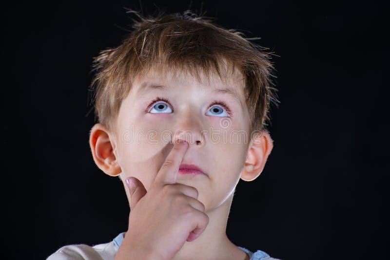 Il ragazzo seleziona il suo naso e cerca, contro un fondo nero fotografia stock libera da diritti