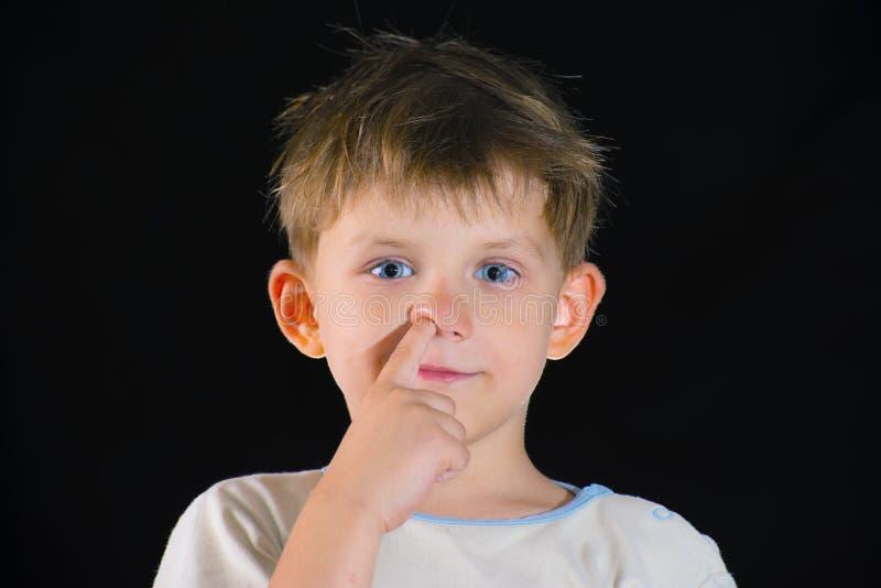 Il ragazzo seleziona il suo naso ed esamina la macchina fotografica, su un fondo nero fotografie stock
