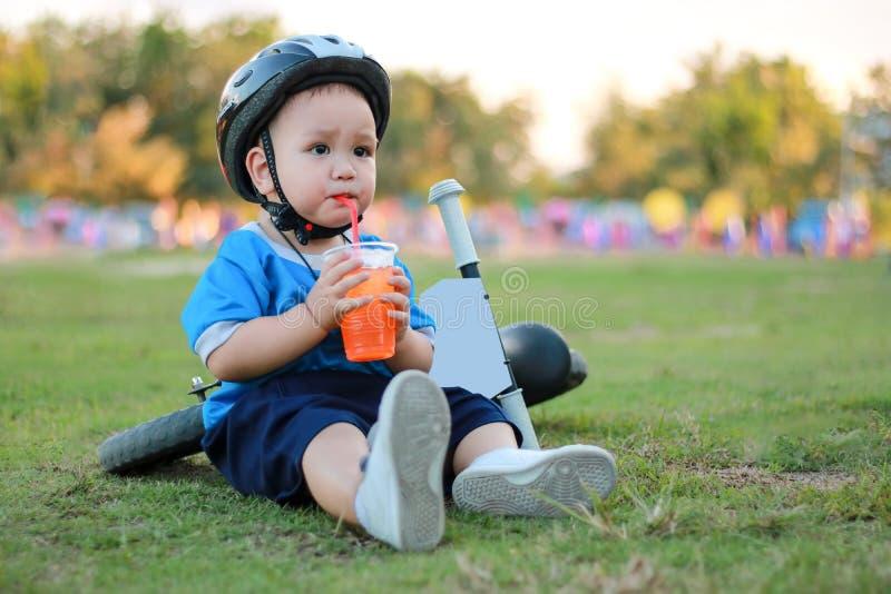 Il ragazzo si è seduto e bevuto l'acqua sul prato inglese accanto alla bici fotografia stock libera da diritti