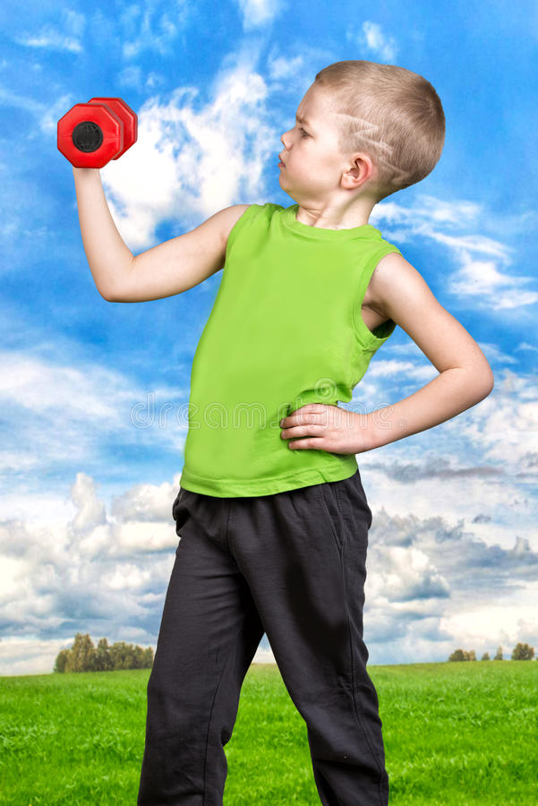 Il ragazzo si esercita con le teste di legno, nell'aria fresca Sport, uno stile di vita sano immagine stock