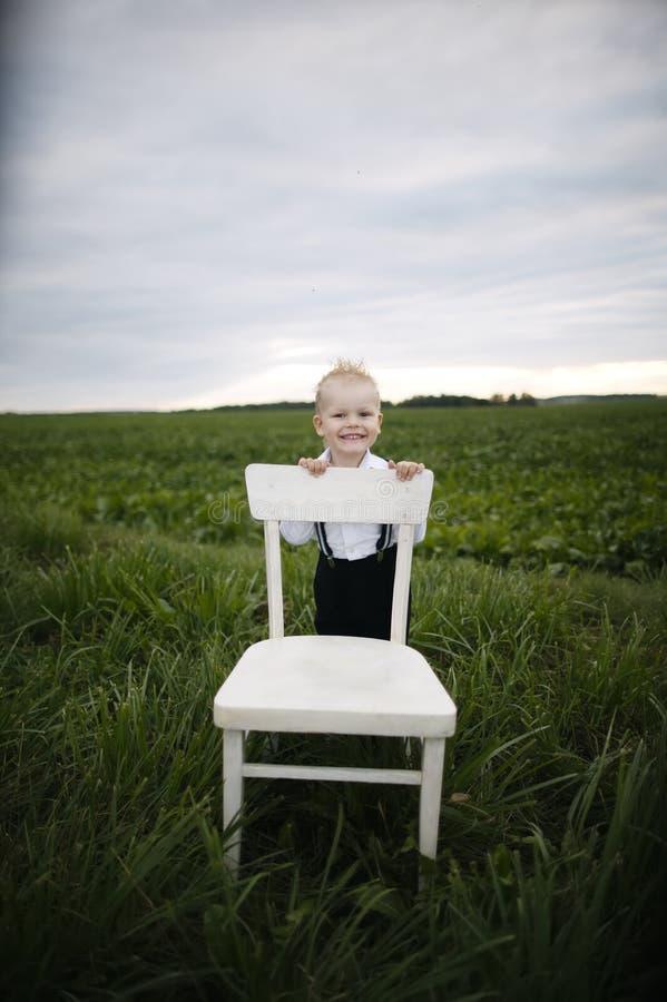 Il ragazzo si siede sulla sedia nel campo immagini stock