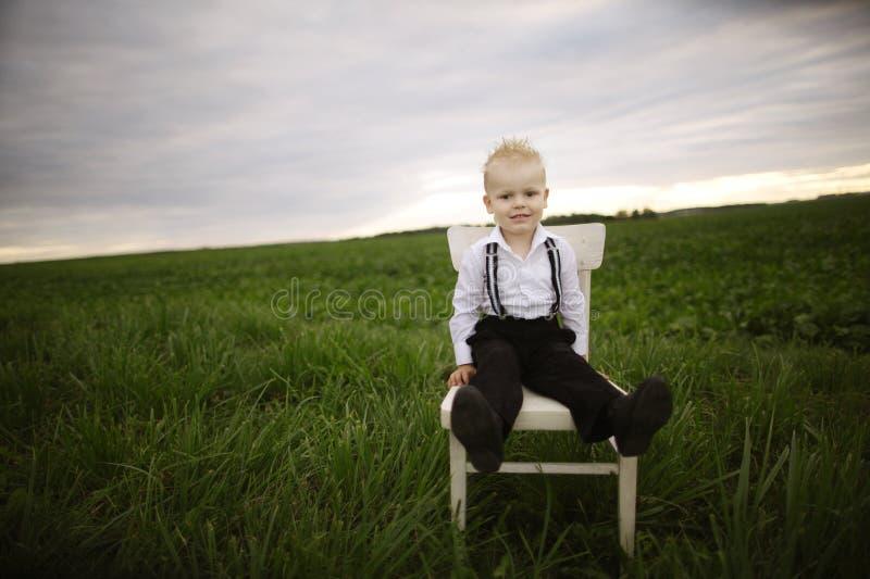 Il ragazzo si siede sulla sedia nel campo fotografia stock libera da diritti