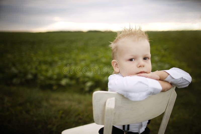 Il ragazzo si siede sulla sedia nel campo immagine stock