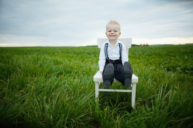 Il ragazzo si siede sulla sedia nel campo immagini stock libere da diritti