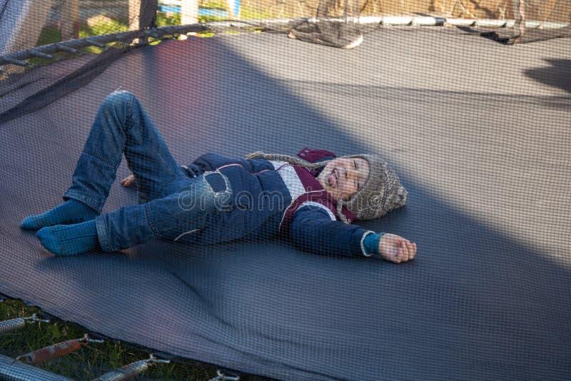 Il ragazzo si trova su un trampolino e sui sorrisi immagini stock