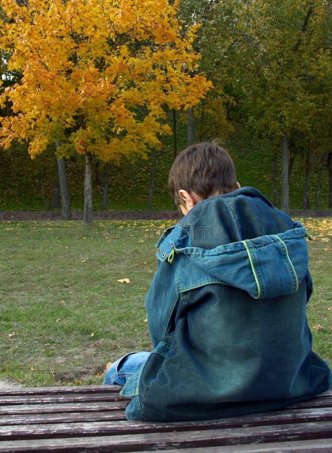 Il ragazzo solo sta sedendosi su un banco fotografia stock libera da diritti