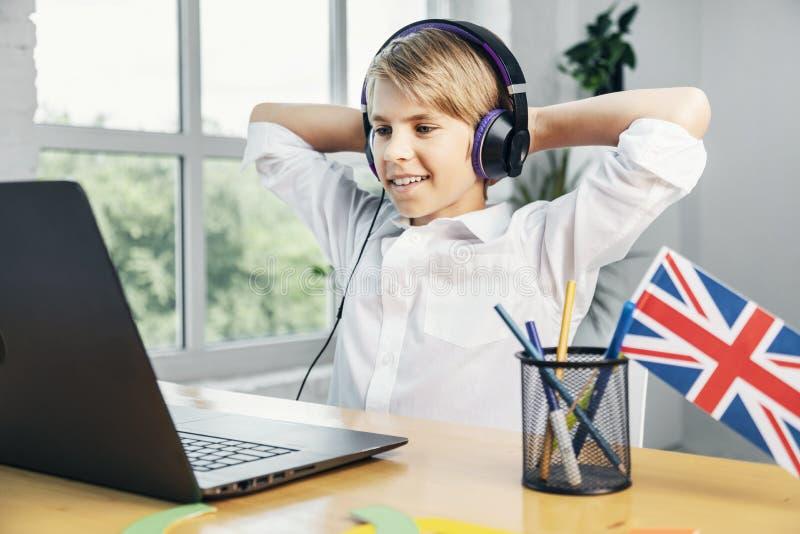 Il ragazzo sorridente è soddisfatto con il suo progresso in inglese fotografia stock libera da diritti