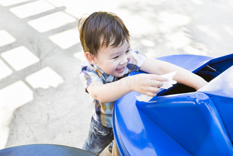 Il ragazzo sorridente della corsa mista che dispone la carta in ricicla il recipiente immagine stock
