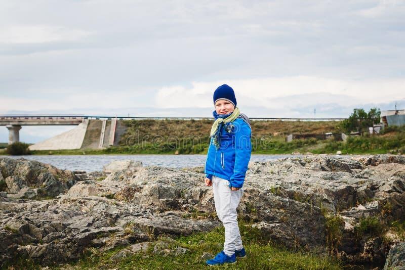 Il ragazzo sorridente nei supporti blu della giacca a vento sulle pietre vicino al fiume in primavera fotografia stock libera da diritti