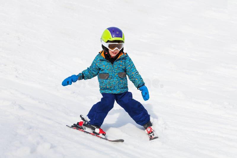 Il ragazzo sorridente nella passamontagna impara la corsa con gli sci fotografia stock