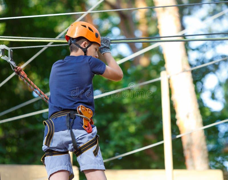 Il ragazzo sportivo, giovane, sveglio in maglietta bianca passa il suo tempo in parco della corda di avventura in casco ed attrez immagine stock