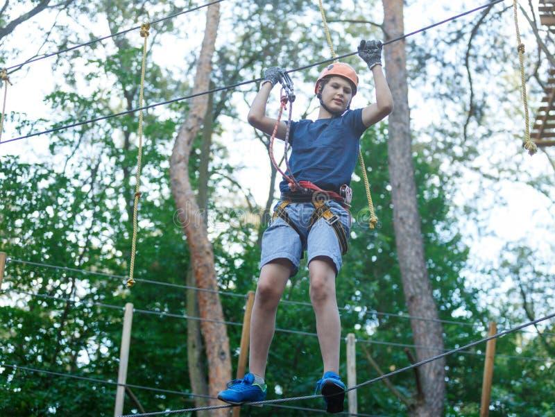 Il ragazzo sportivo, giovane, sveglio in maglietta bianca passa il suo tempo in parco della corda di avventura in casco ed attrez fotografie stock libere da diritti