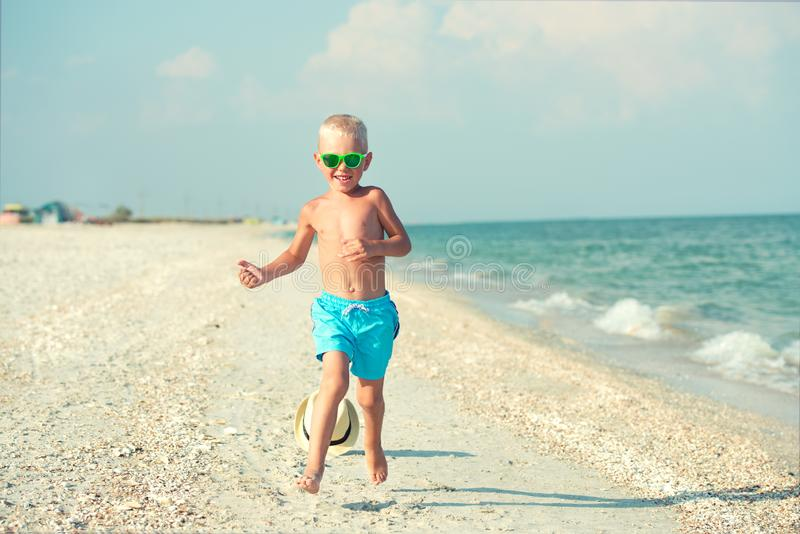 Il ragazzo sta correndo lungo la spiaggia Lle vacanze estive felici fotografia stock libera da diritti