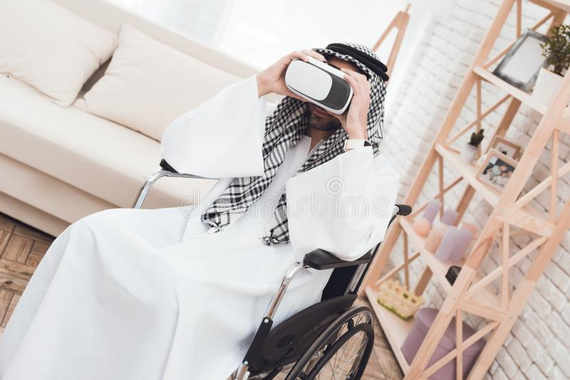 Il ragazzo sta dietro un uomo arabo in una sedia a rotelle che esamina i vetri di realtà virtuale immagine stock