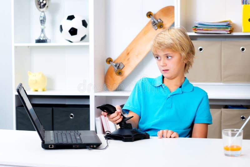 Il ragazzo sta giocando il gioco di computer fotografia stock libera da diritti