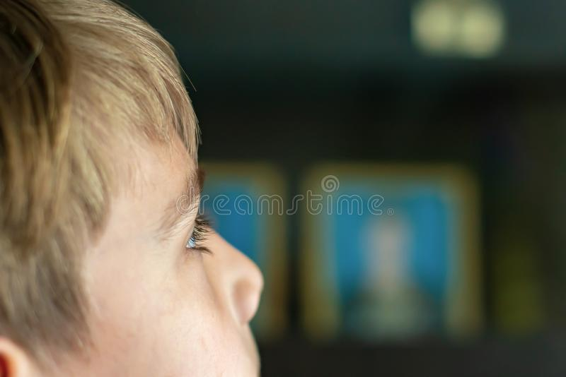 Il ragazzo sta guardando la TV, gli occhi del bambino è vicino su, contro lo sfondo di una televisione funzionante fotografia stock