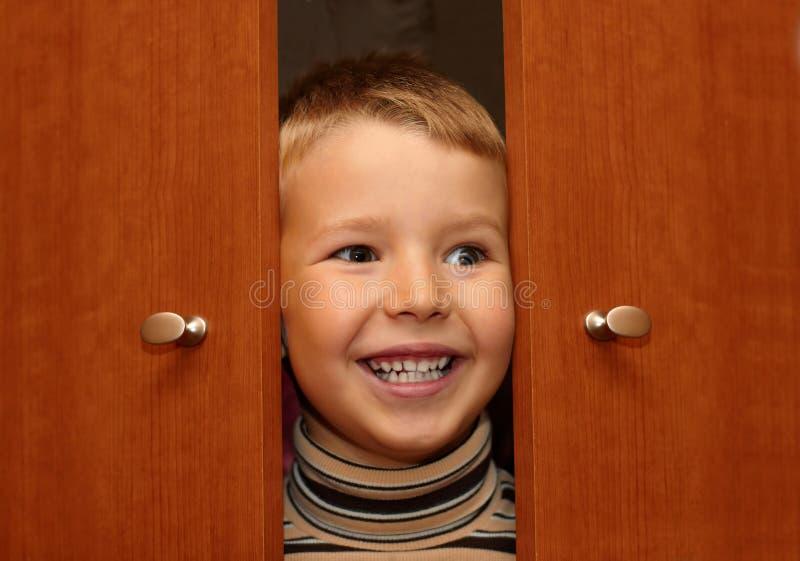 Il ragazzo sta nascondendosi in un guardaroba fotografia stock libera da diritti
