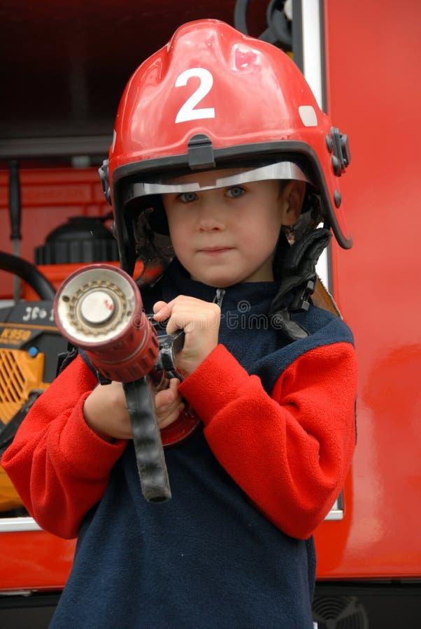 Il ragazzo sta sedendosi in un camion dei vigili del fuoco fotografia stock libera da diritti