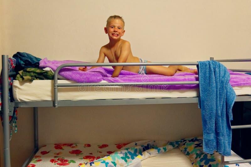 Il ragazzo sta trovandosi su un letto di cuccetta immagine stock libera da diritti