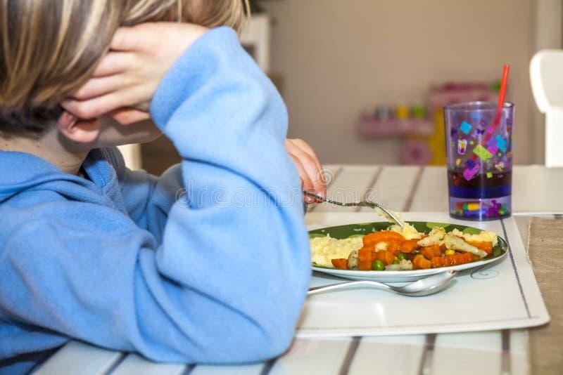 Il ragazzo stanco non gradisce mangiare il suo pranzo fotografia stock