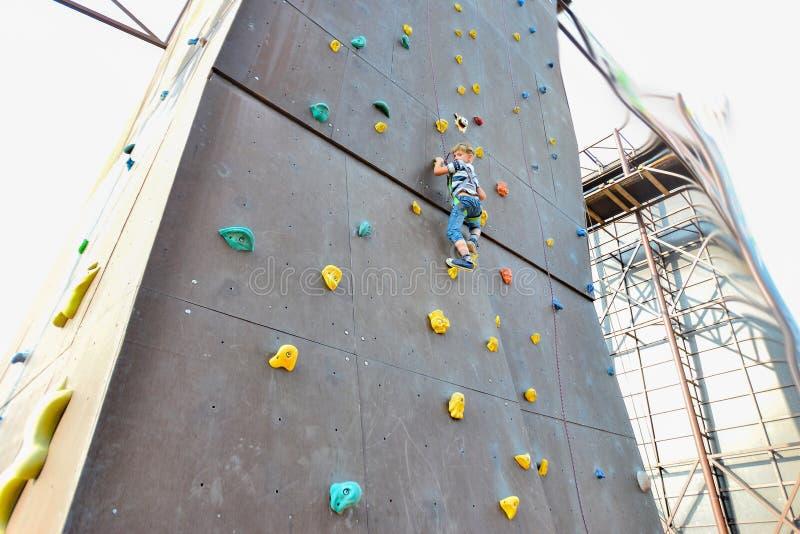 Il ragazzo sulle torri degli scalatori, supera gli ostacoli in un parco estremo fotografia stock libera da diritti