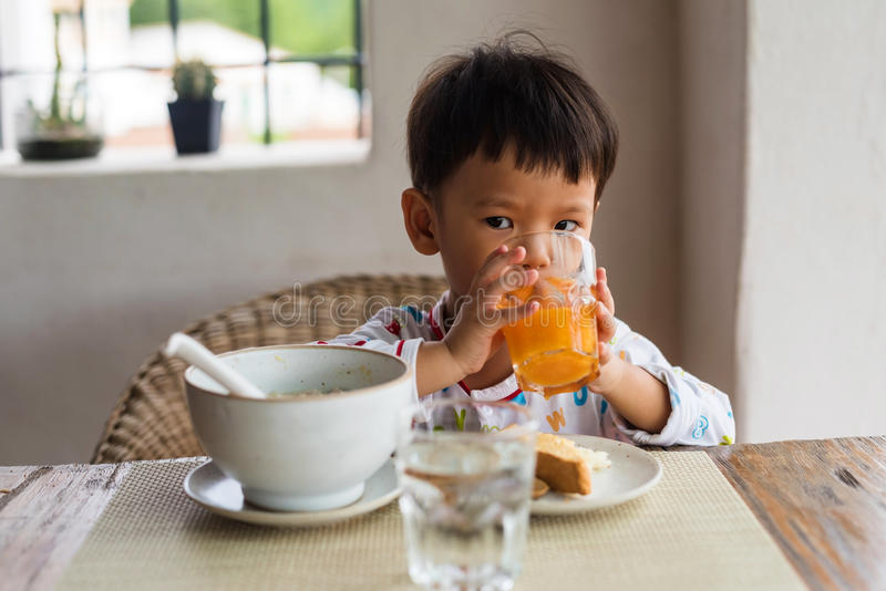 Il ragazzo sveglio asiatico ha la prima colazione e succo d'arancia immagine stock