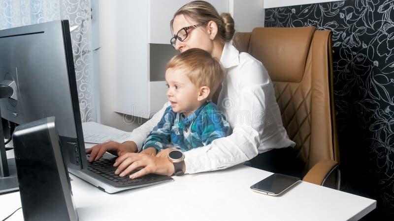 Il ragazzo sveglio del bambino che si siede sulle madri avvolge il lavoro nell'ufficio fotografia stock