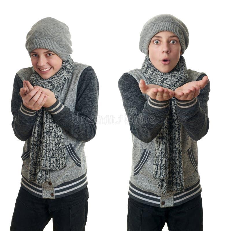 Il ragazzo sveglio dell'adolescente in maglione grigio sopra bianco ha isolato il fondo immagini stock