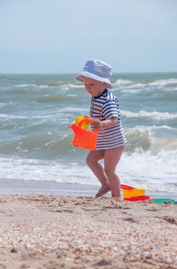 Il ragazzo sveglio gioca un secchio sulla spiaggia immagini stock libere da diritti