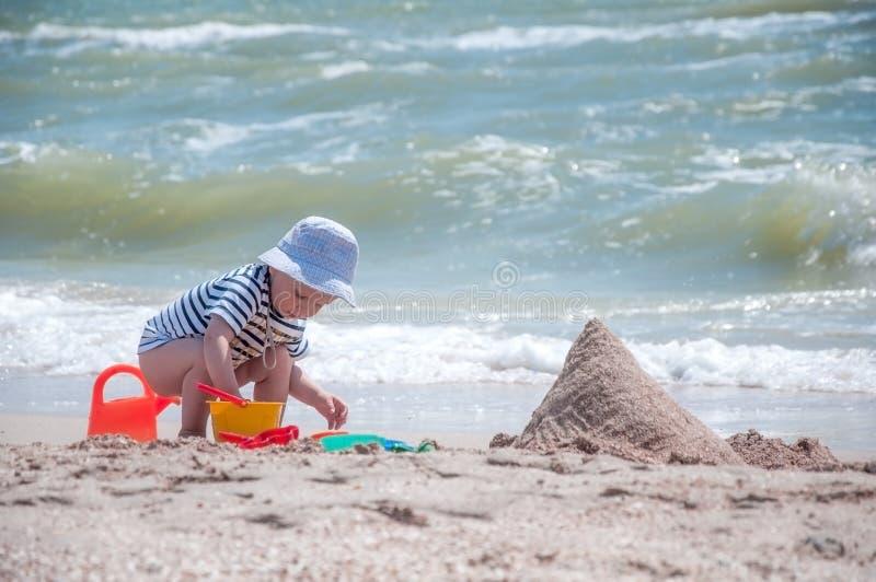 Il ragazzo sveglio gioca un secchio sulla spiaggia fotografia stock libera da diritti