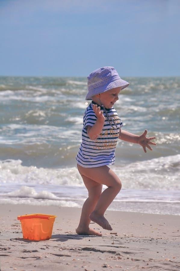 Il ragazzo sveglio gioca un secchio sulla spiaggia immagini stock