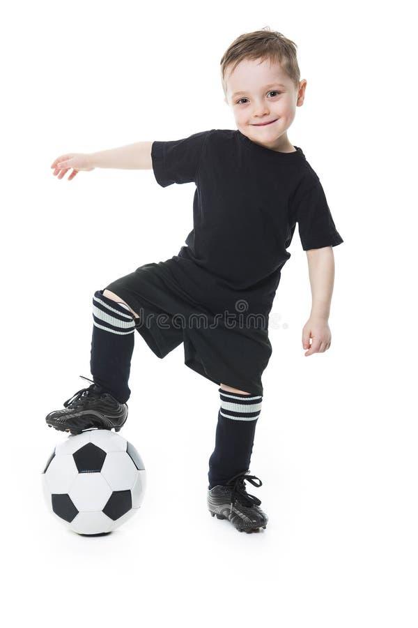 Il ragazzo sveglio sta giudicando una palla di calcio isolata su fondo bianco Calcio immagini stock