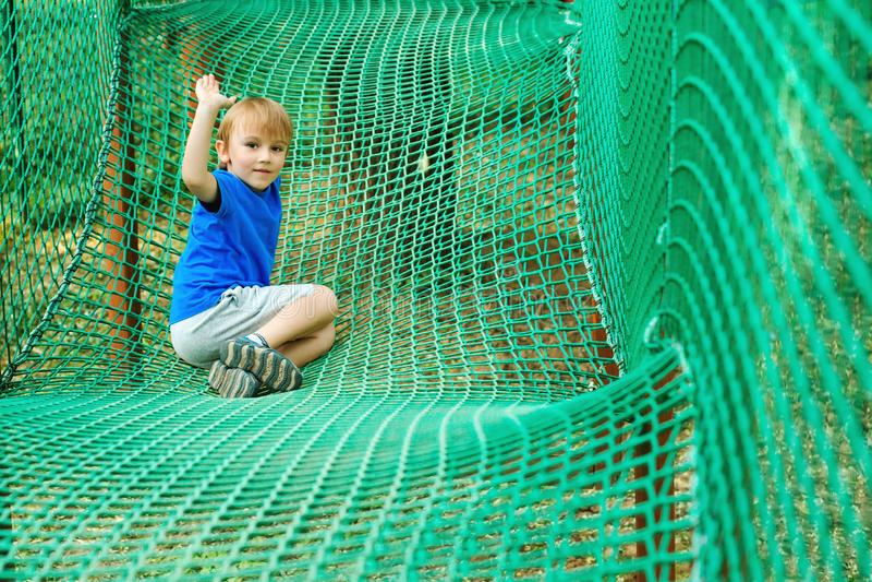 Il ragazzo sveglio supera gli ostacoli nel parco di avventura della corda Concetto di vacanze estive Bambino felice che gioca al  immagini stock