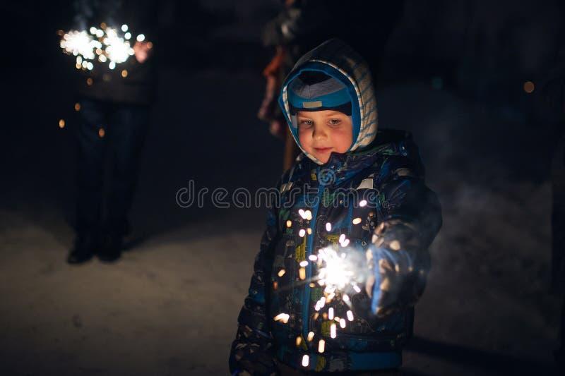 Il ragazzo tiene una stella filante in sue mani mentre celebra un nuovo anno sulla via alla notte immagine stock libera da diritti