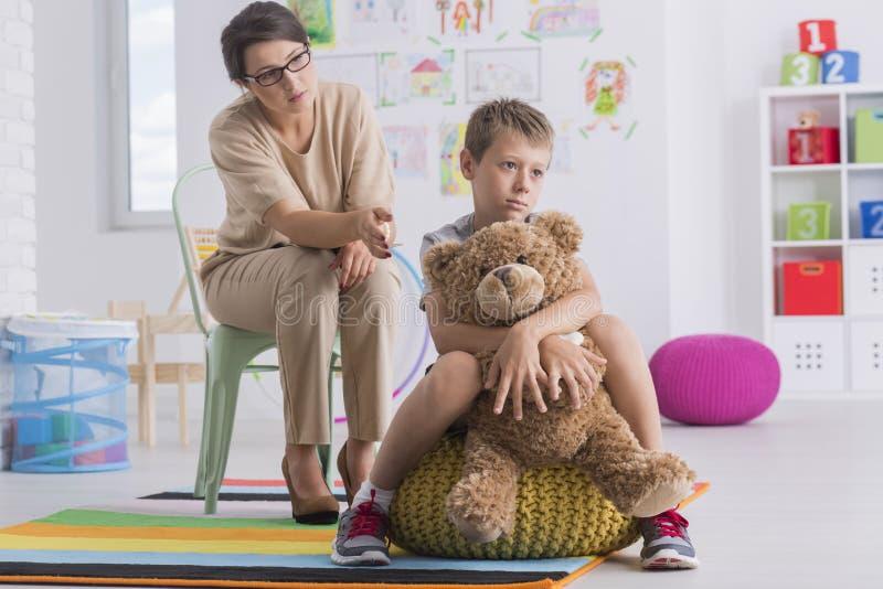 Il ragazzo triste abbraccia l'orsacchiotto fotografie stock
