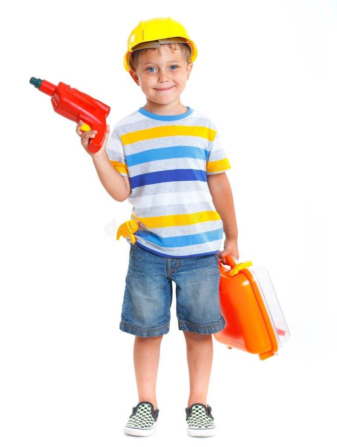 Il ragazzo in un casco gioca nel costruttore immagine stock libera da diritti