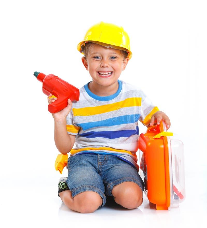 Il ragazzo in un casco gioca nel costruttore fotografia stock libera da diritti
