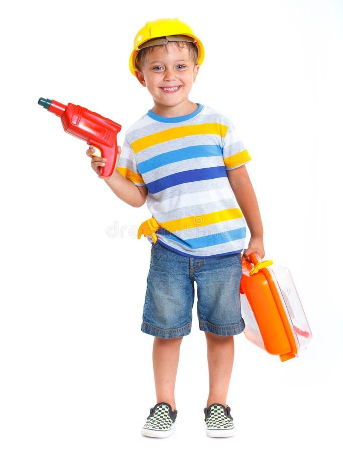 Il ragazzo in un casco gioca nel costruttore fotografie stock