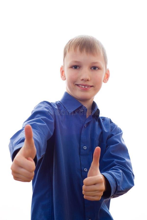Il ragazzo in una camicia blu si leva in piedi e sorride immagine stock libera da diritti