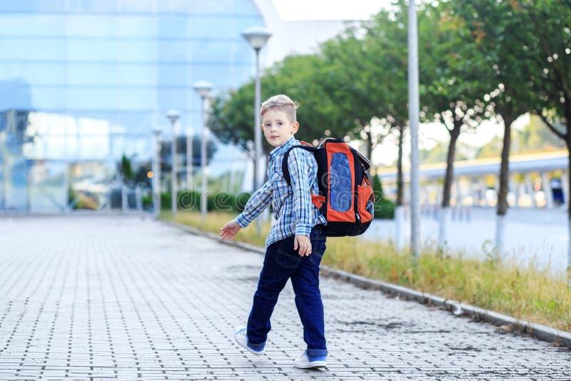 Il ragazzo va a scuola con uno zaino Il concetto dell'infanzia, dell'istruzione e della scuola fotografia stock