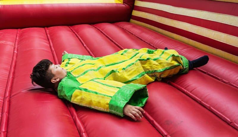 Il ragazzo in vestito di plastica variopinto sta trovandosi nel castello rimbalzante immagine stock libera da diritti