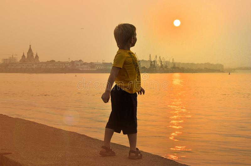 Il ragazzo vicino al fiume esamina un bello tramonto immagini stock libere da diritti