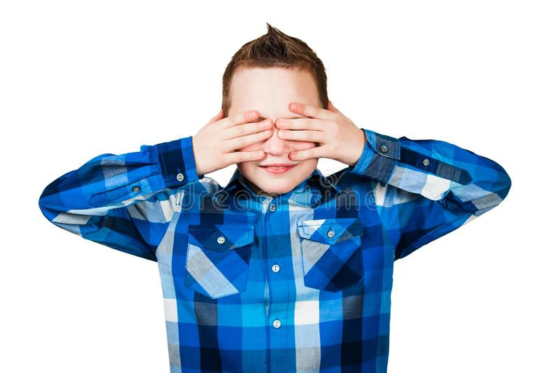 Il ragazzo vicino i suoi occhi con le sue mani Isolato su priorit? bassa bianca fotografia stock