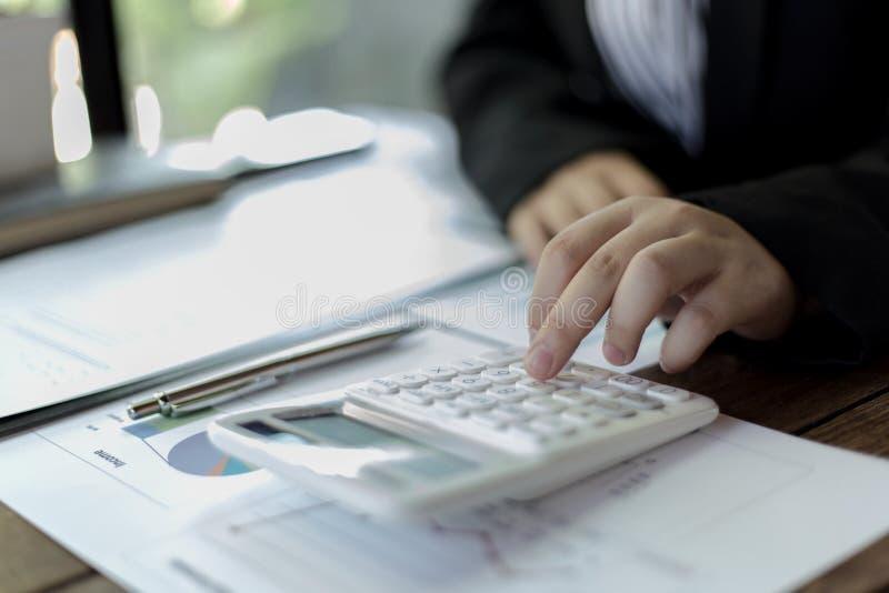 Il ragioniere femminile della societ? sta controllando il conto finanziario della societ? immagini stock libere da diritti