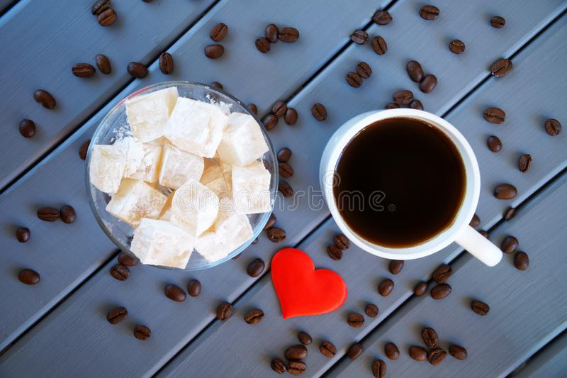 Il rahat tradizionale classico di lukum - tazza orientale della squisitezza con caffè, grani arrostiti e cuore rosso Di legno immagine stock