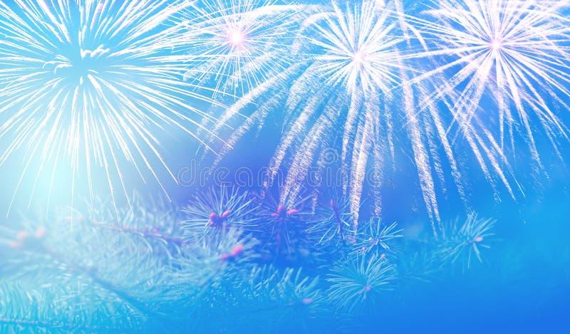 Il ramo del pino di Natale su un bello fondo blu con le scintille ed i fuochi d'artificio spruzza, l'umore del nuovo anno meravig immagine stock