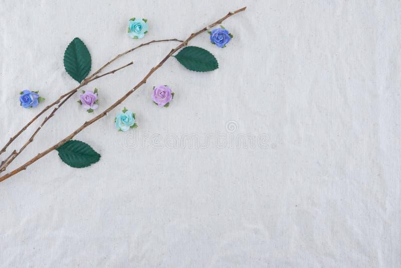 Il ramo di Brown decora con i fiori di carta della rosa blu del tono fotografie stock