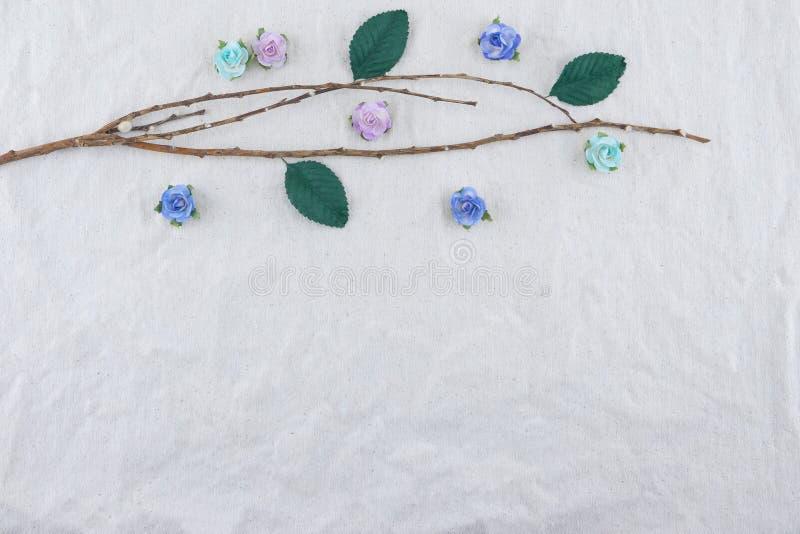 Il ramo di Brown decora con i fiori di carta della rosa blu del tono immagini stock